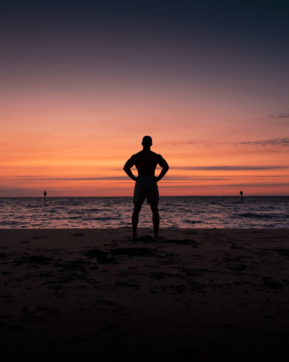 silhouette of man and woman standing on beach during sunset