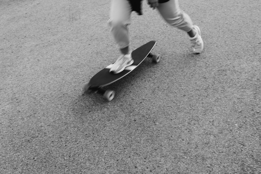 person in white pants and black shoes holding black skateboard