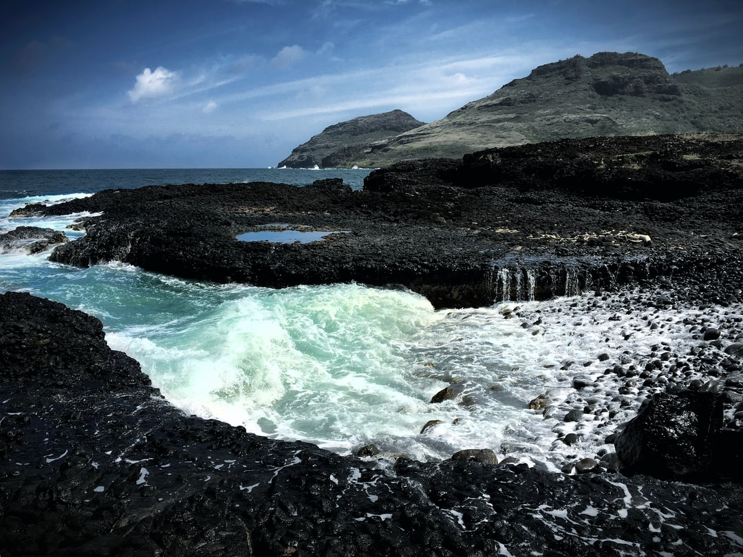 The Pacific Ocean flows over volcanic rock in Maui, Hawaii.