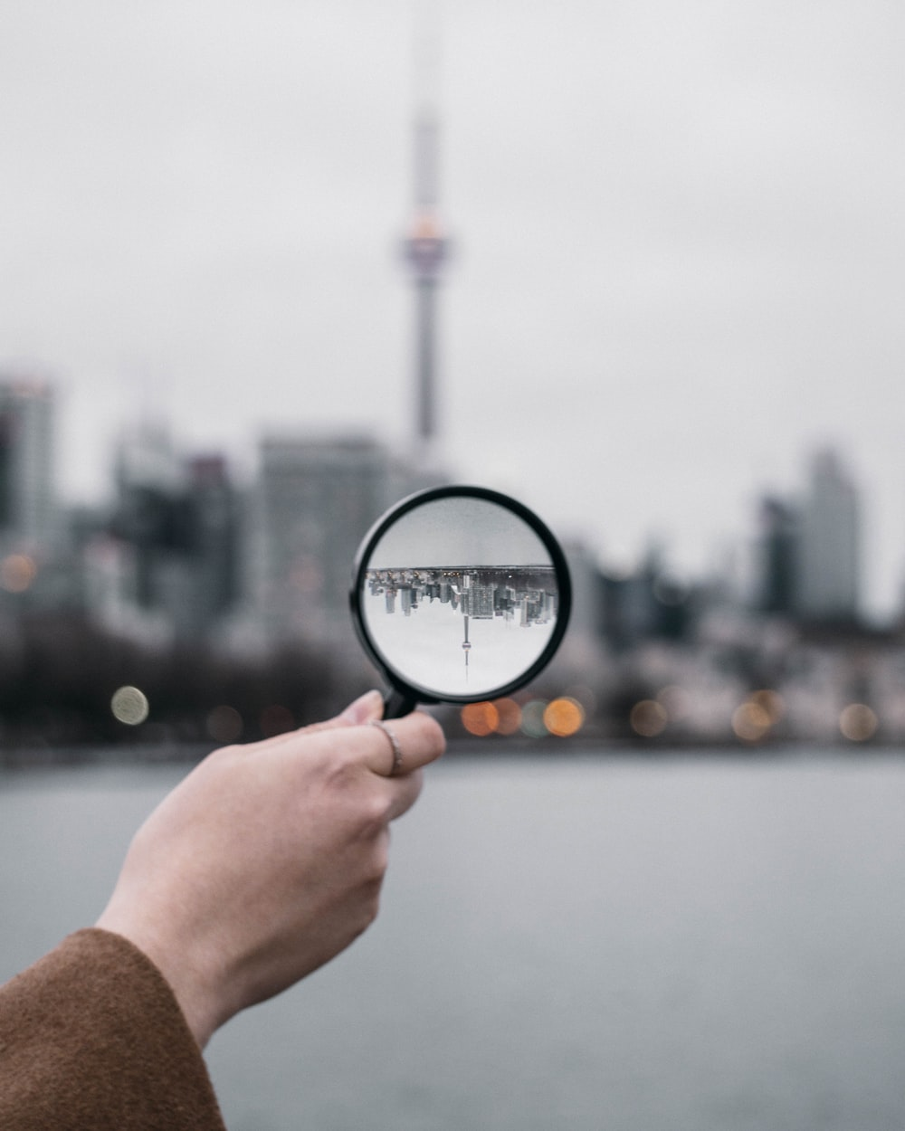 person holding magnifying glass during daytime
