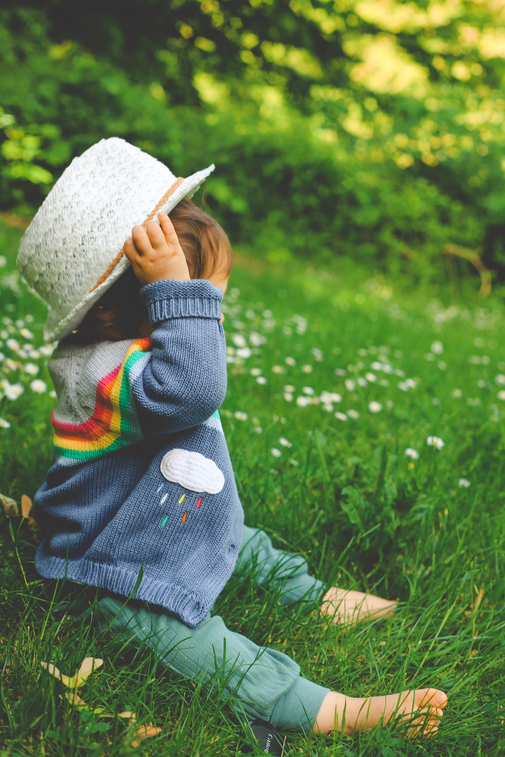 child in gray jacket and white hat standing on green grass field during daytime