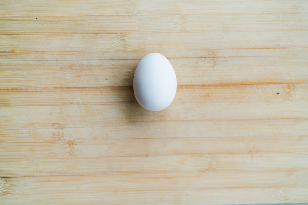 white egg on brown wooden table