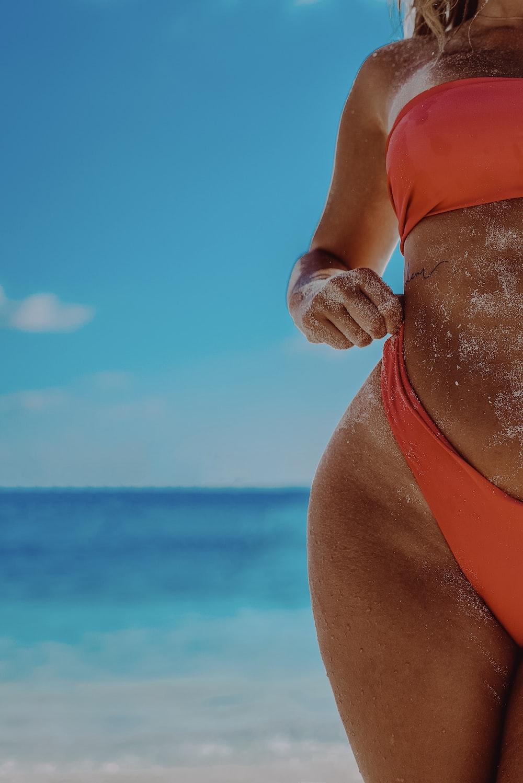 woman in red bikini bottom on beach during daytime