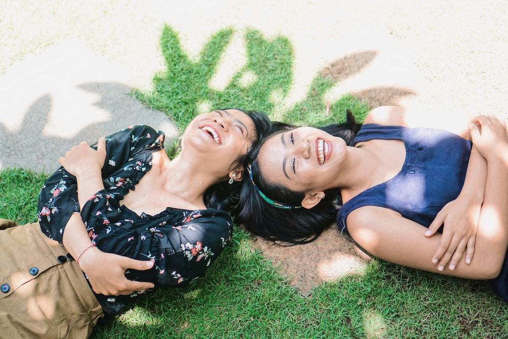 2 women lying on green grass field during daytime