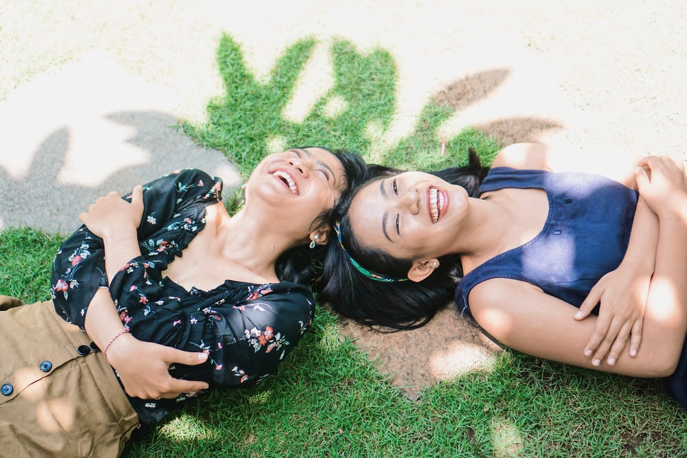 2 women lying on green grass field during daytime