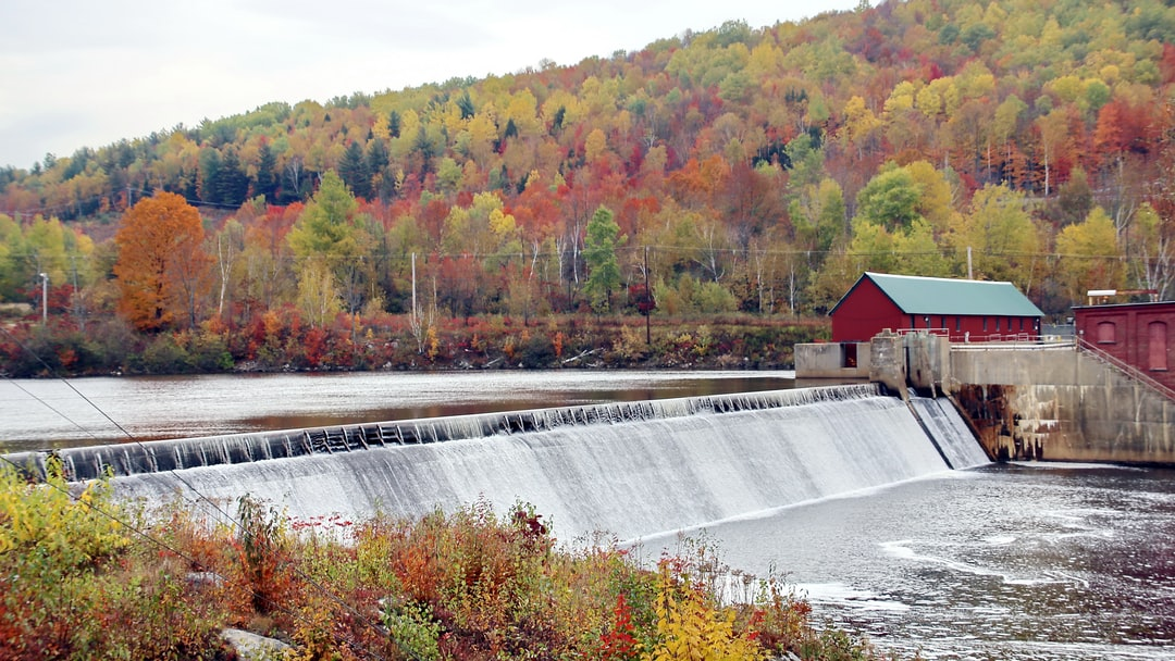 """A suitable picture for """"waterfall management"""" models: a weir in Berlin (NH, USA) dams the river Androscoggin; surrounded by trees in Indian Summer colors.  Parts of the river's water is used for producing hydro power in this town."""