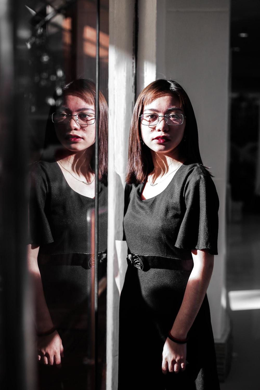 woman in black blazer standing beside glass window