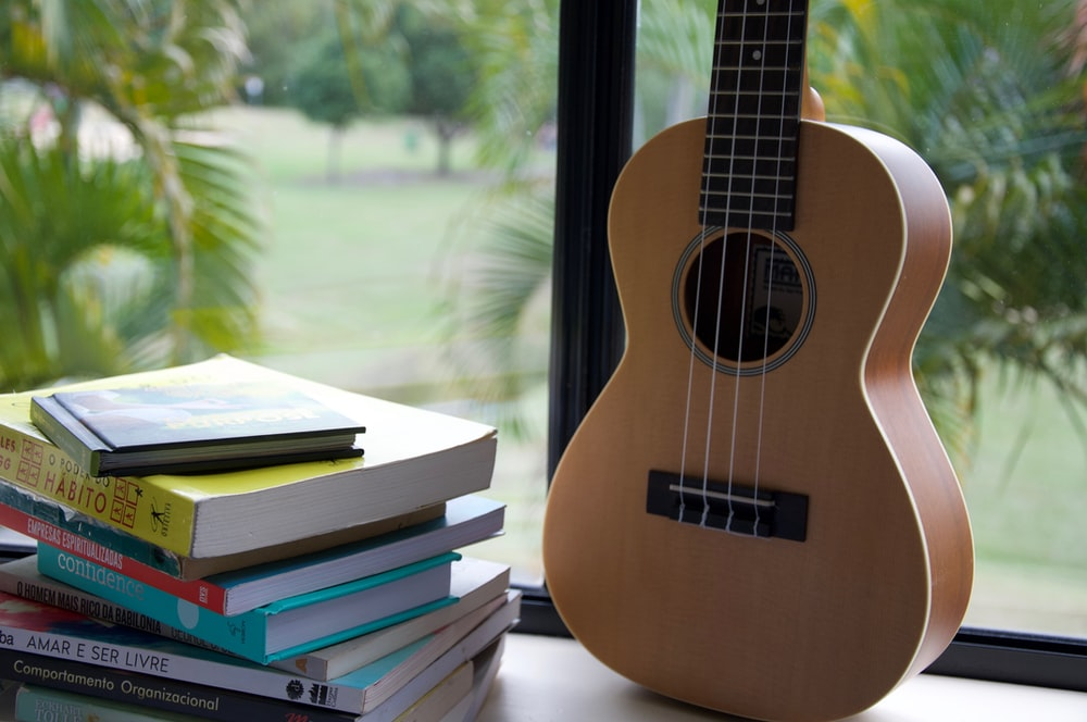 brown acoustic guitar on books