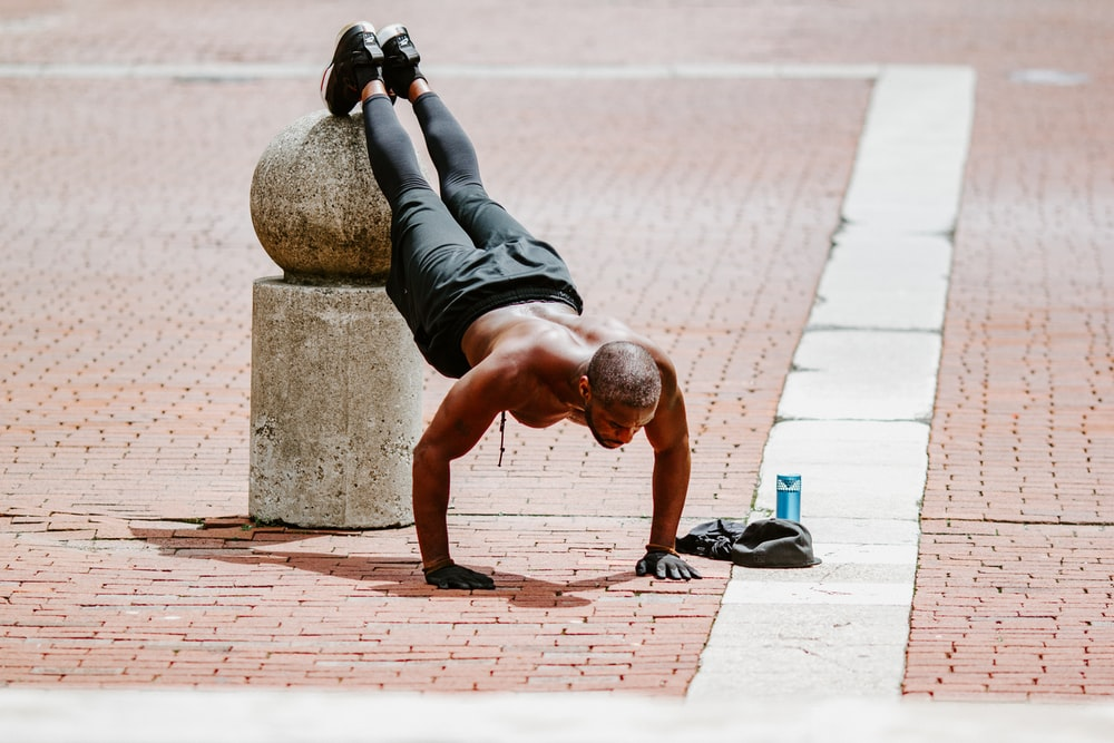 man in black tank top and black shorts lying on brown concrete floor during daytime
