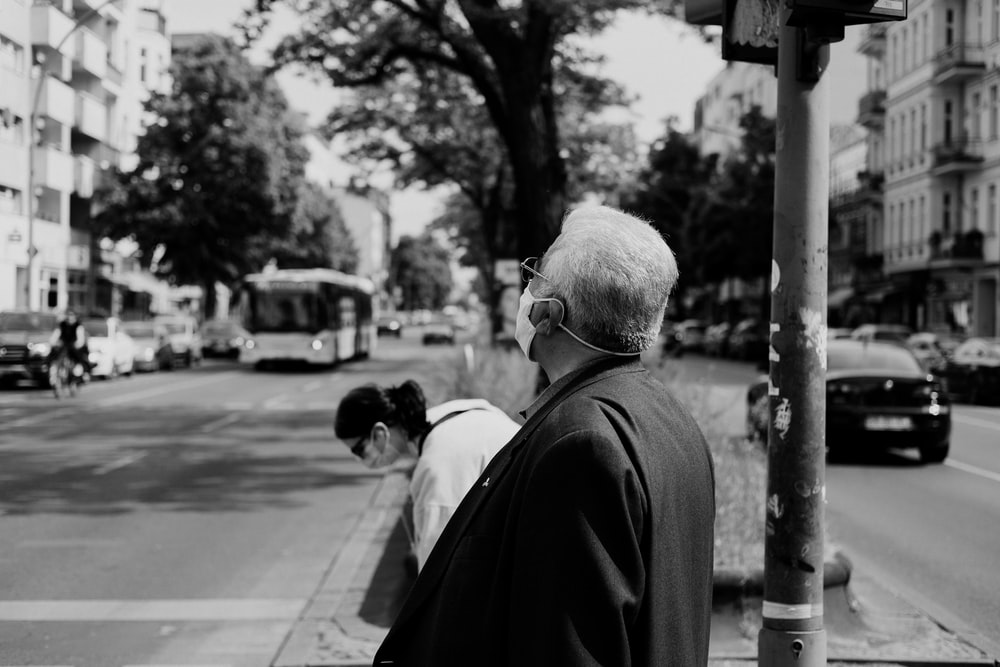 man in black suit standing on sidewalk in grayscale photography