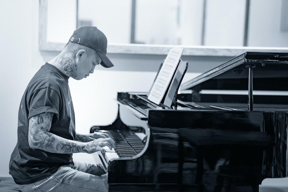 man in black long sleeve shirt playing piano