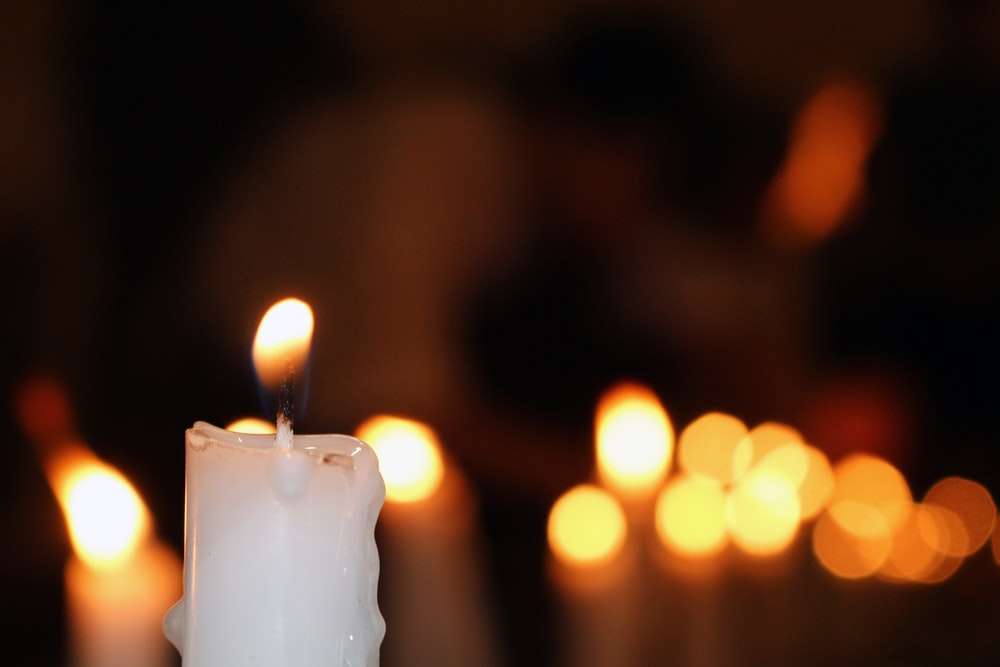 white pillar candle with bokeh lights