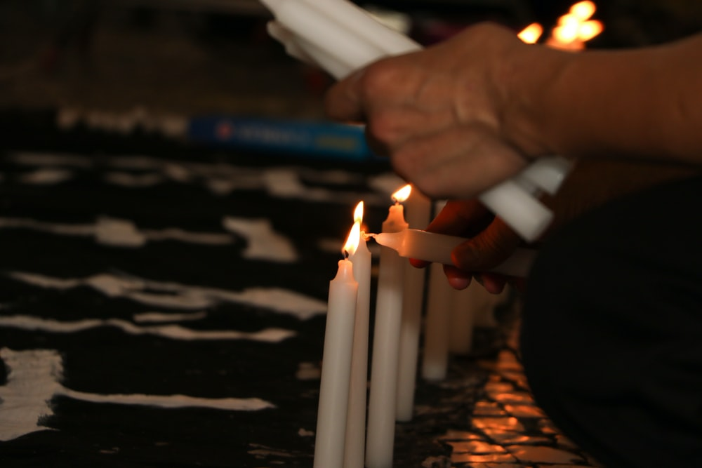person holding white candles with fire