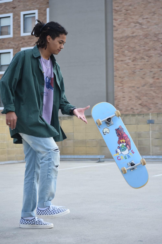 man in purple jacket holding blue skateboard
