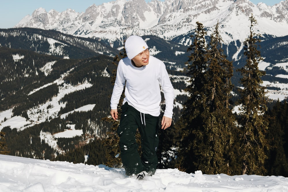 man in white hoodie standing on snow covered ground
