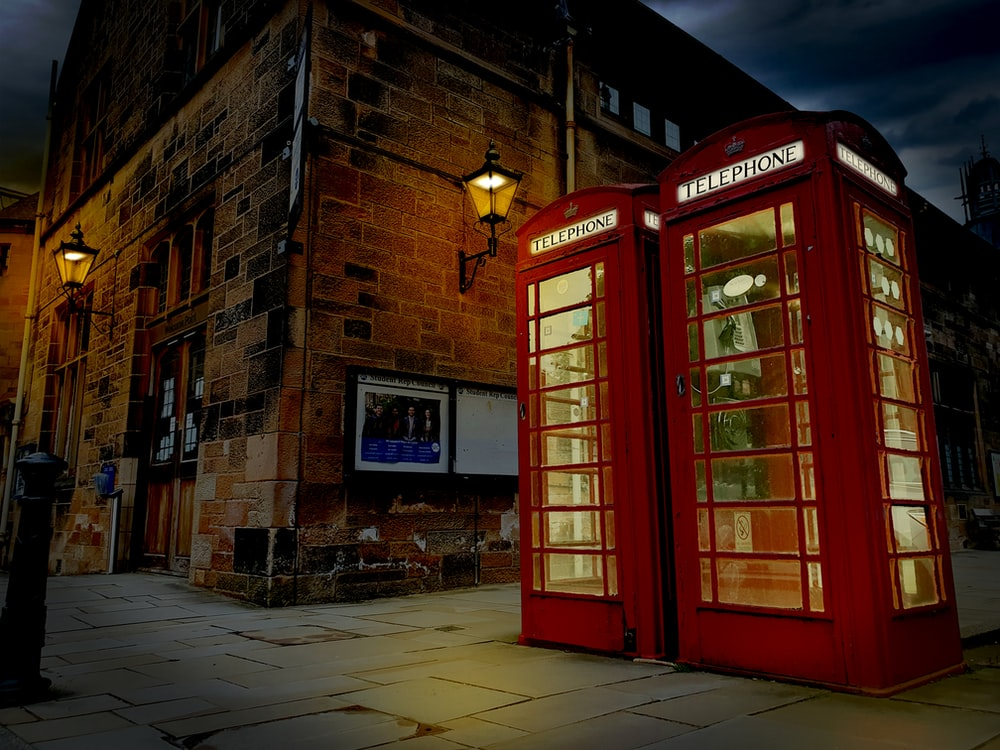 red telephone booth in front of brown brick building