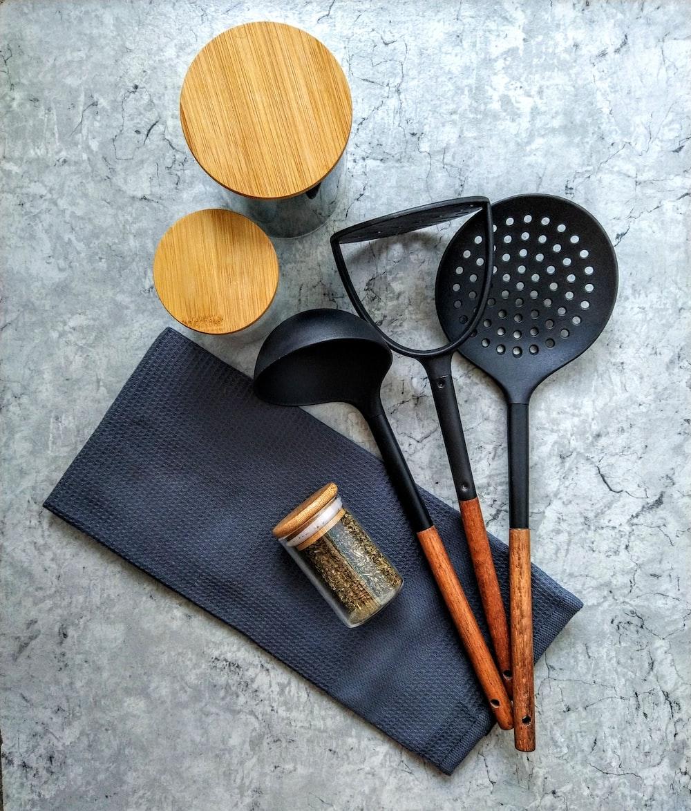 brown wooden spatula beside black handled spatula
