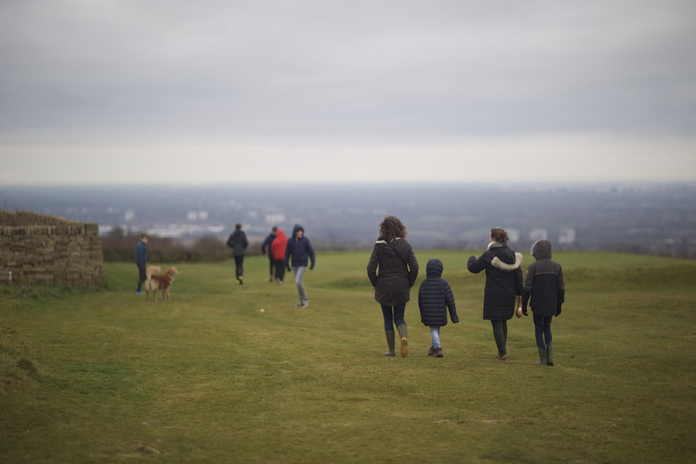 people walking on green grass field during daytime