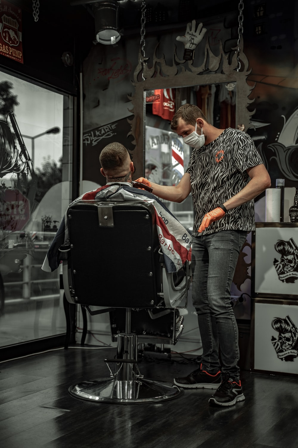 man in black and white shirt sitting on barber chair