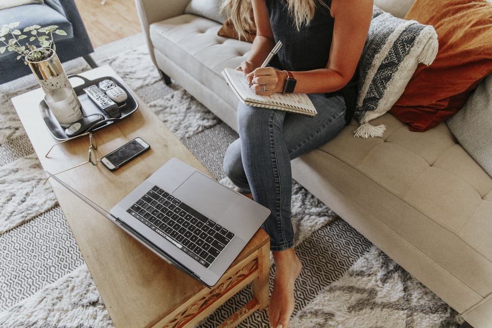 woman in black and white tank top and blue denim jeans sitting on white couch