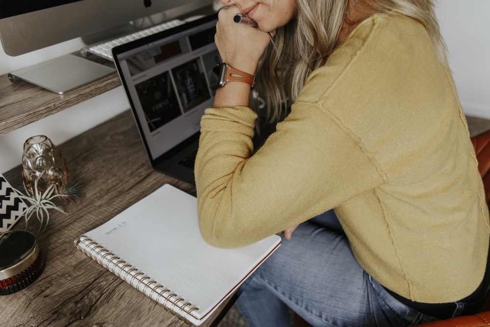 woman in brown long sleeve shirt and blue denim jeans sitting on brown wooden table
