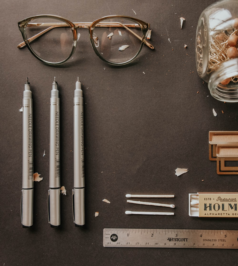 black framed eyeglasses beside white pen and brown framed eyeglasses