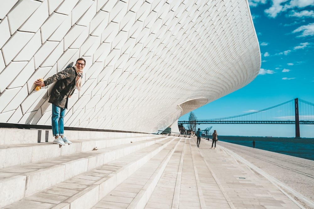 woman in black jacket and blue denim jeans walking on white concrete pathway during daytime