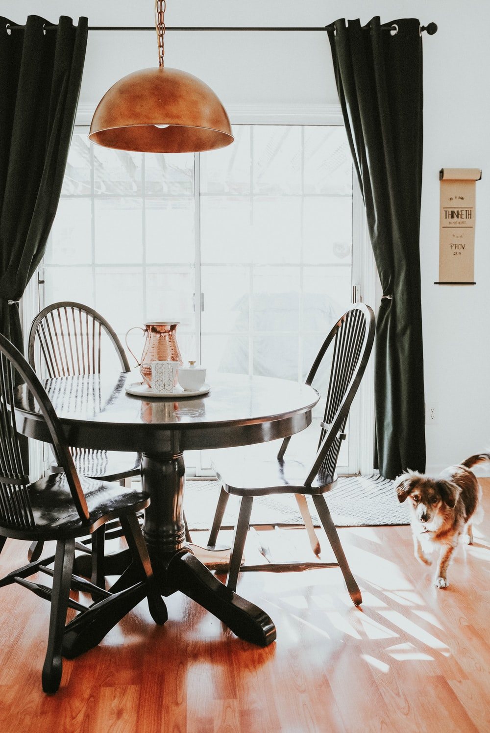 brown and white short coated dog on brown wooden round table