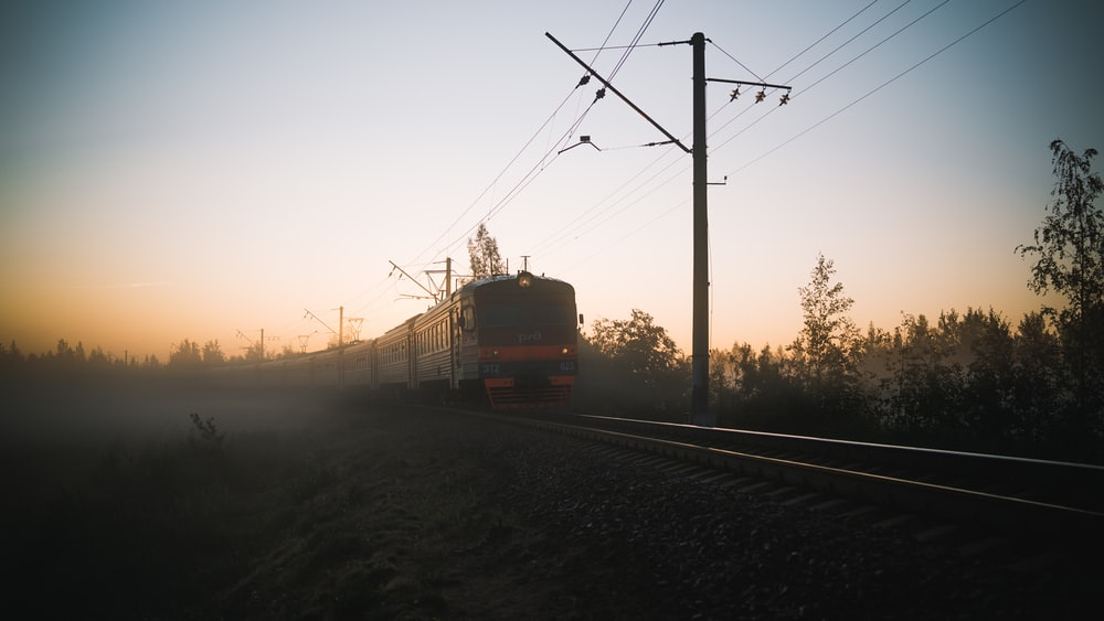 red and white train on rail road during sunset