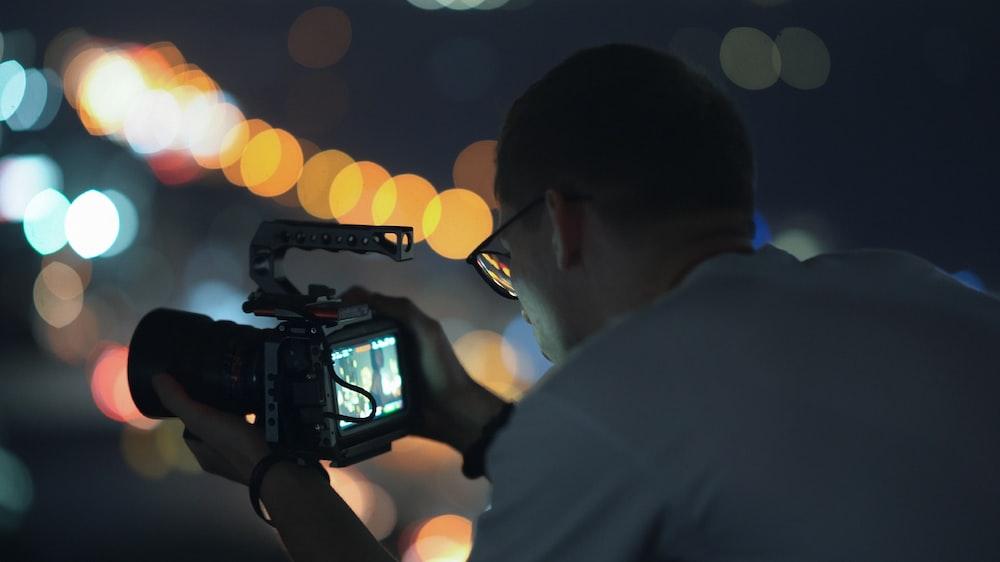 man in white shirt holding black video camera