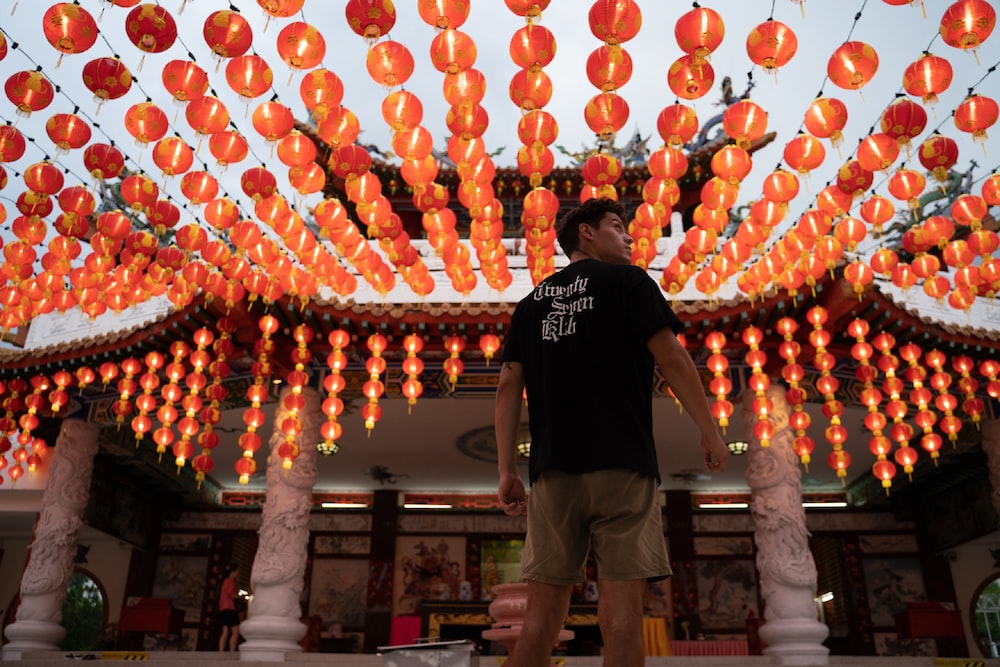 man in black crew neck t-shirt standing near red and yellow balloons