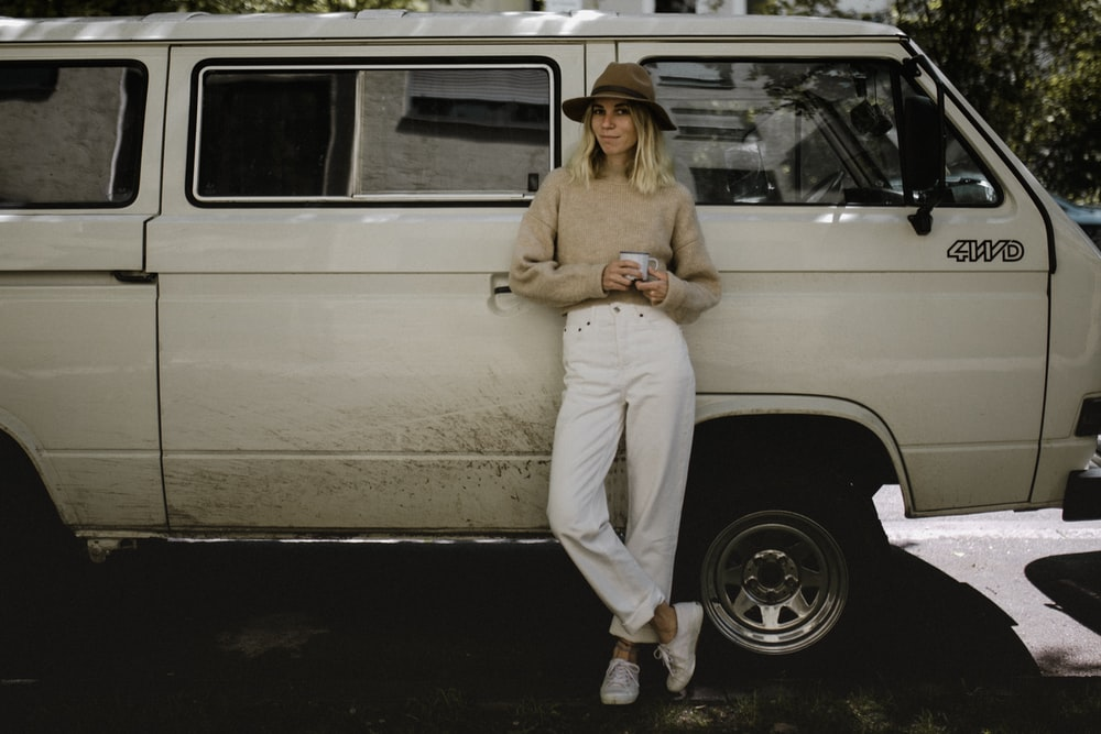 woman in beige long sleeve shirt and white pants sitting on white car