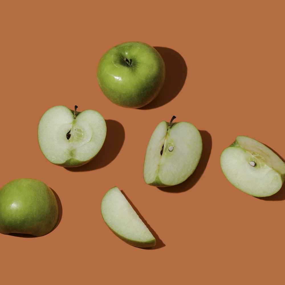green apple fruit on pink surface