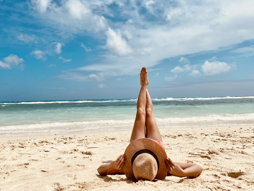 woman in brown sun hat sitting on beach shore during daytime