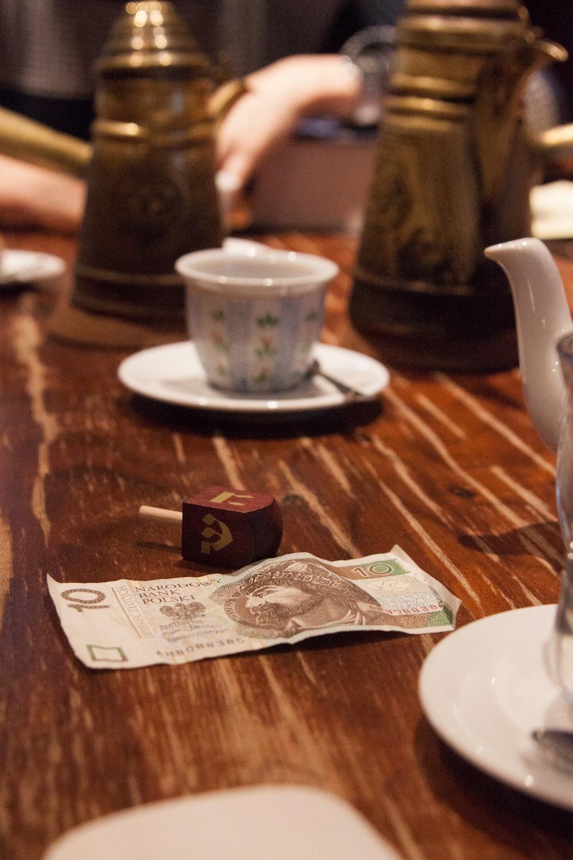 20 banknote beside white ceramic mug on brown wooden table