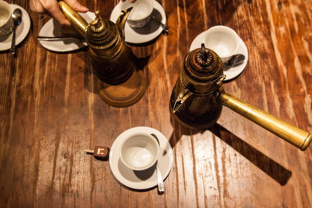white ceramic teacup on saucer beside brown ceramic teapot