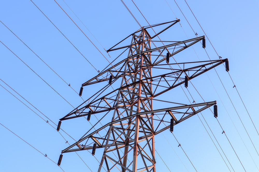 brown and gray electric towers under blue sky during daytime