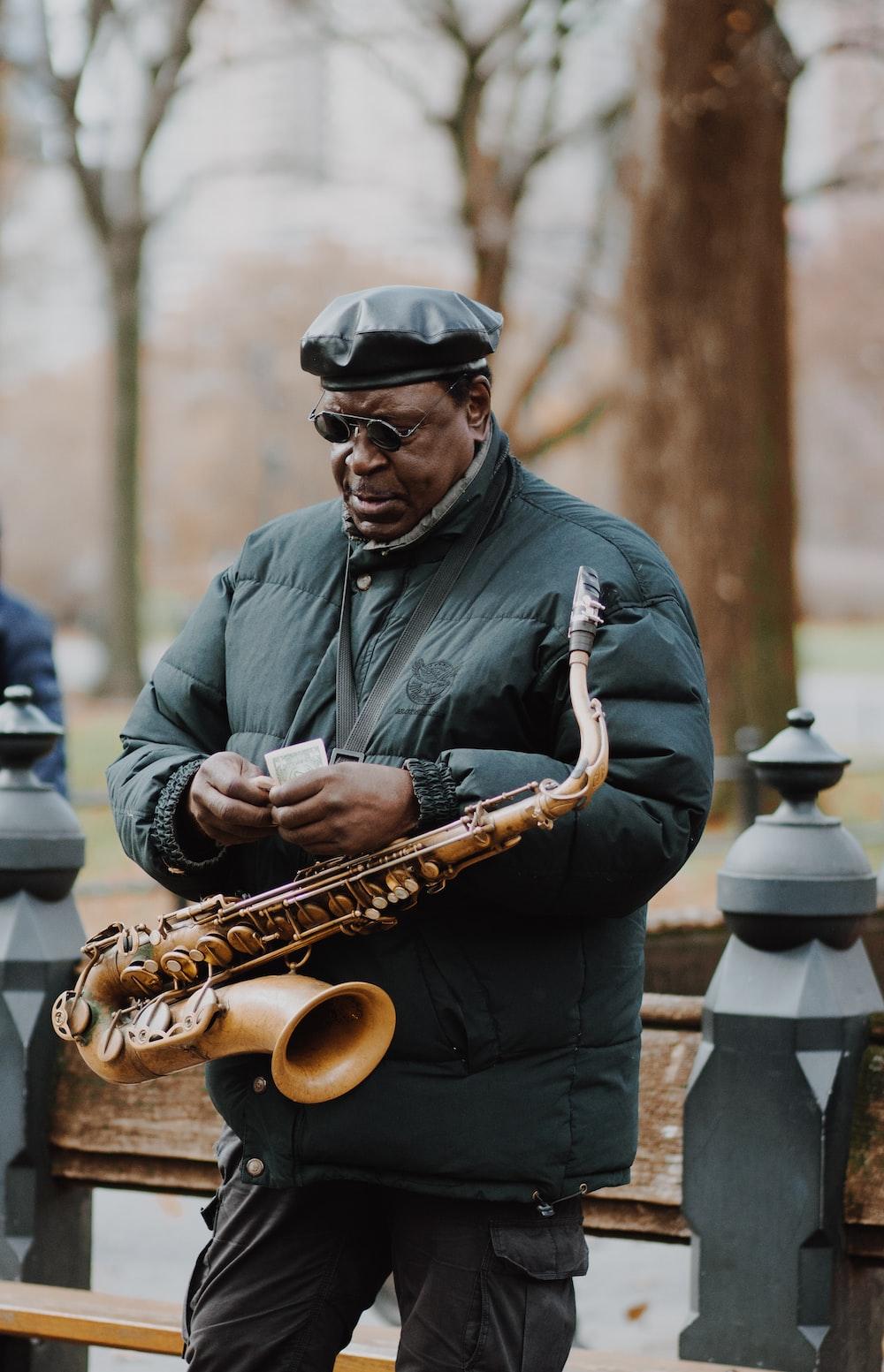 man in gray dress shirt playing saxophone