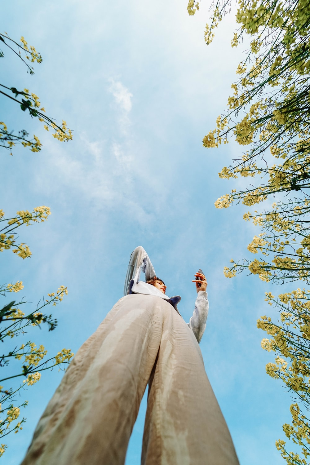 low angle photography of woman in white dress standing under green tree during daytime
