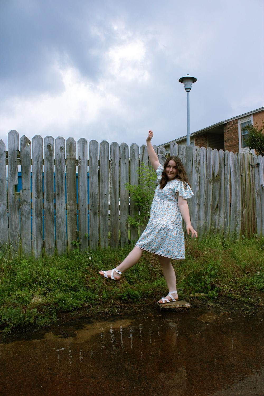 woman in blue dress standing beside wooden fence