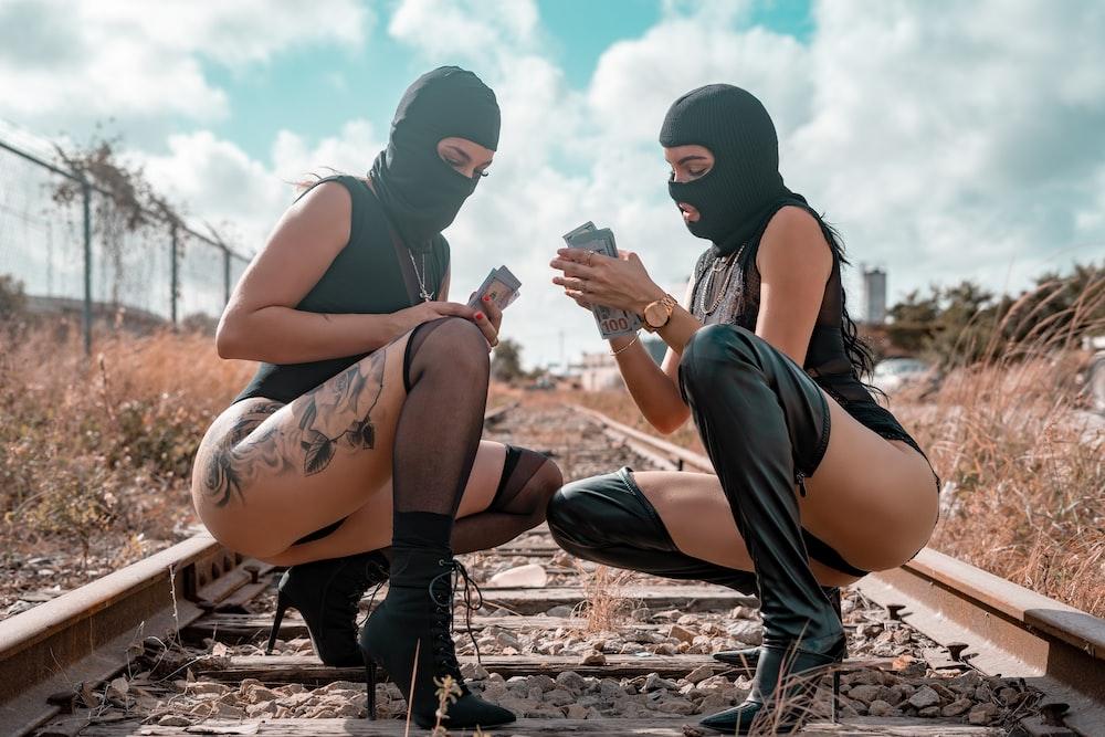 2 women wearing black mask sitting on brown rock during daytime