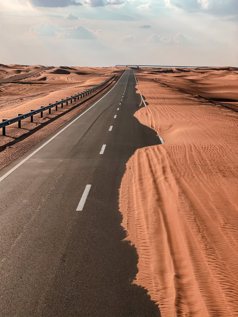 black asphalt road in the middle of desert