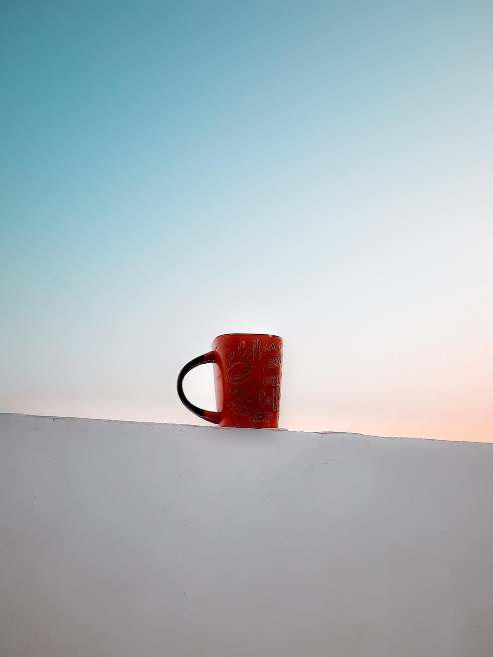 red ceramic mug on white table