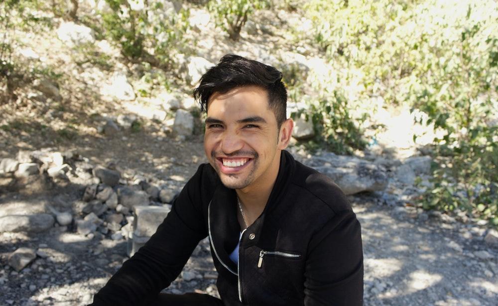 man in black zip up jacket smiling