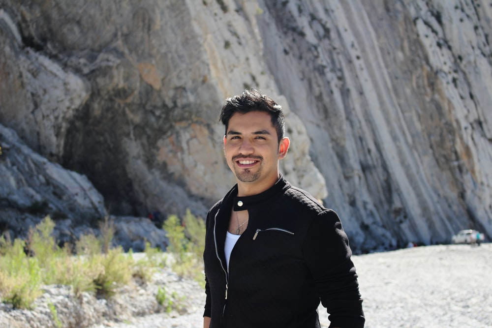 man in black jacket standing near gray rock formation during daytime