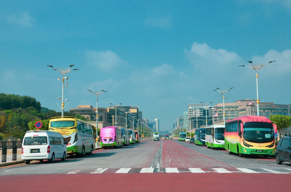 cars on road near city buildings during daytime