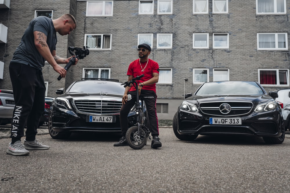 man in red polo shirt and black pants riding on black mercedes benz car