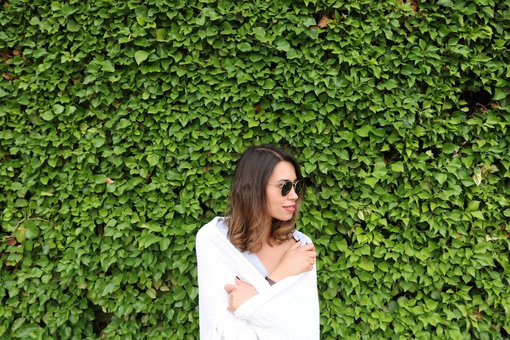 woman in white long sleeve shirt standing beside green plants