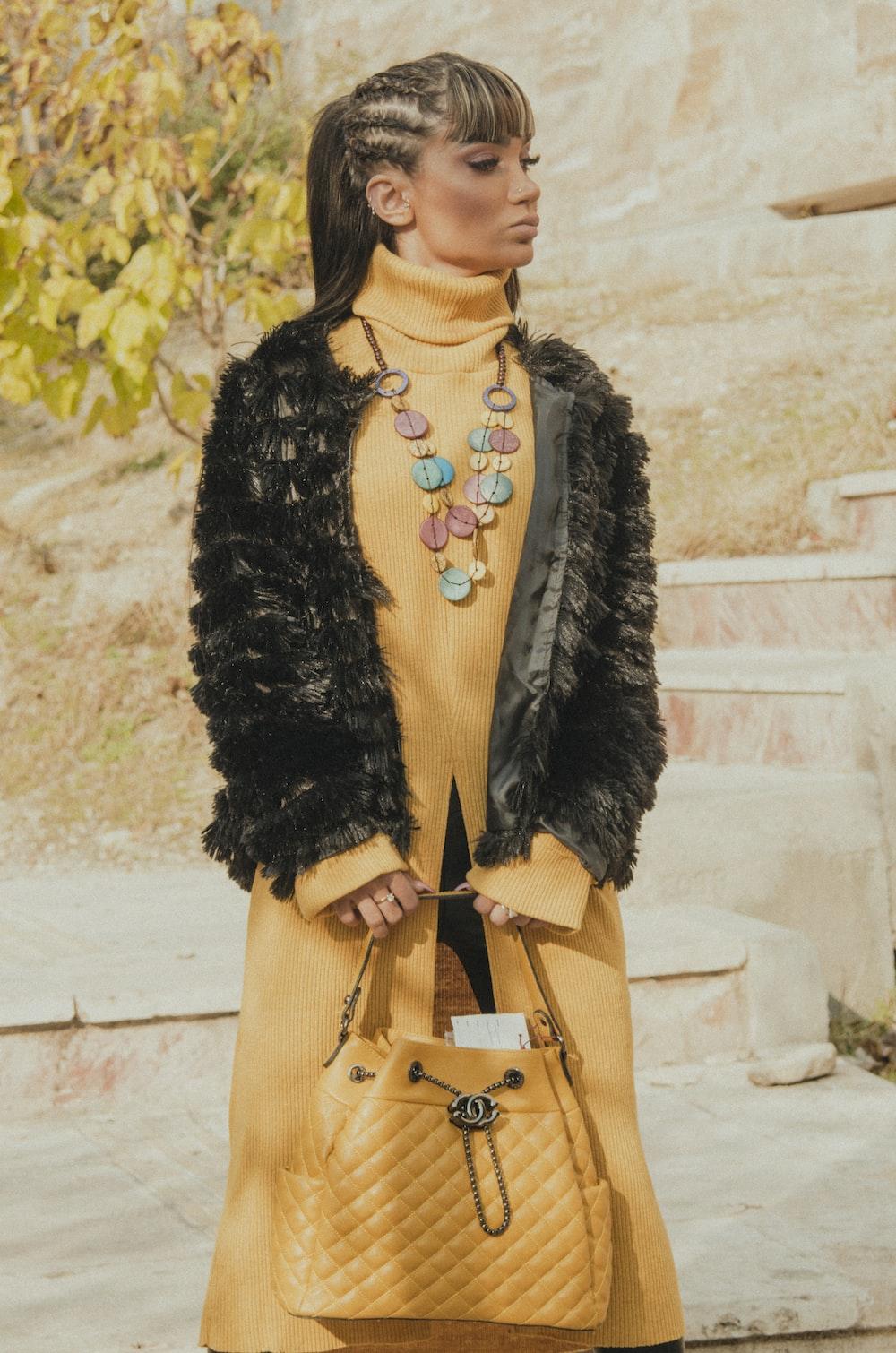 woman in black fur coat and brown sling bag