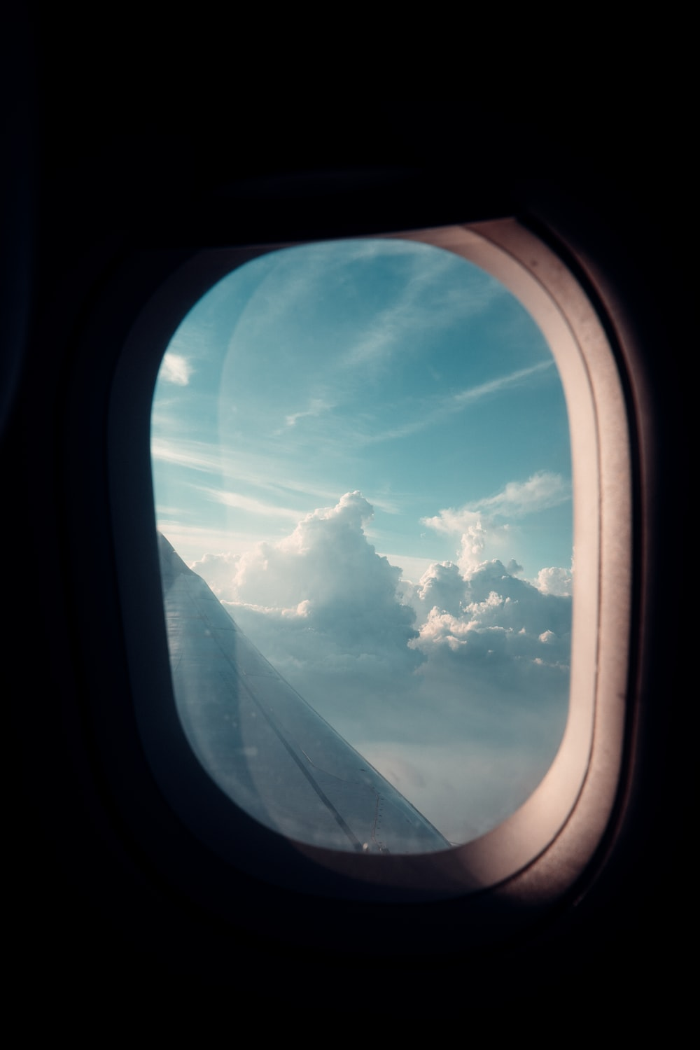 airplane window view of clouds during daytime